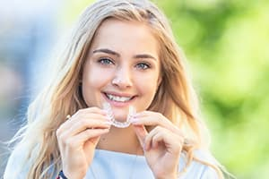 Woman inserting Invisalign teeth alignment device